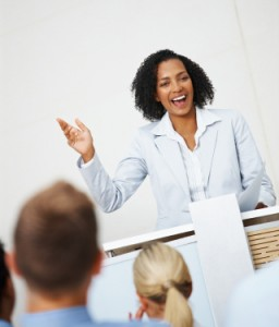 Smiling business woman addressing a group of people